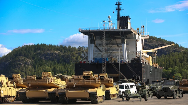 M1A1 Abrams Main Battle Tanks and other vehicles and equipment are staged for transportation at the designated offload pier during a pre-planned Single Ship Movement and offload of military equipment from a Maritime Prepositioning Force ship in the Trøndelag region of Norway. U.S. Marines from 2nd Marine Logistics Group out of Camp Lejeune, NC, in coordination with their Norwegian counterparts, are modernizing some of the equipment currently stored within six caves as a part of the Marine Corps Prepositioning Program-Norway by placing approximately 350 containers of gear and nearly 400 pieces of heavy rolling stock into the storage caves.  Specific equipment which will greatly increase the program's readiness includes M1A1 Main Battle Tanks, Tank Retrievers, Armored Breeching Vehicles, Amphibious Assault Vehicles, Expanded Capacity Vehicle (ECV) Gun Trucks and several variants of the MTVR 7 ½ ton trucks. Planning for this equipment refresh began in the spring of 2010.