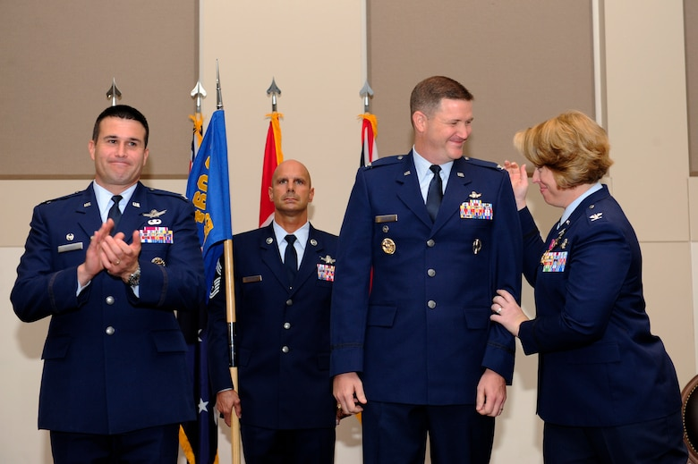 Col. DeAnna Burt, outgoing 460th Operations Group commander, right, congratulates Col. Michael Jackson, 460th OG commander, center, while Col. John Wagner, 460th Space Wing commander, left, applauds during the 460th OG change of command ceremony Aug. 12, 2014, at the Leadership Development Center on Buckley Air Force Base, Colo. Jackson assumed command from Burt, who served as commander of the 460th OG for two years. (U.S. Air Force photo by Airman 1st Class Samantha Saulsbury/Released)