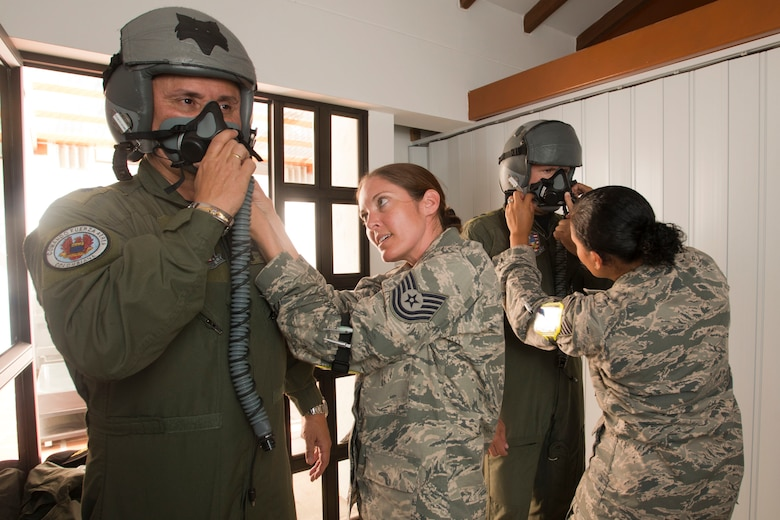 Colombian Air Force Brig. Gen. Carlos Eduardo Bueno and Brig. Gen. Ramses Rueda Rueda (sic) are fitted with flight helmets by U.S. Air Force Tech. Sgt. Hannah Conner and Tech. Sgt. Benita Johnson, both assigned to the 169th Operations Support Squadron's Aircrew Flight Equipment section from McEntire Joint National Guard Base of the South Carolina Air National Guard, Aug. 11, 2014. The fitting is part of the preflight requirements to fly in a SCANG F-16 during Relampago (Lightning) 2014, at Rionegro, Colombia. Relampago is a combined air cooperation engagement with the Republic of Colombia. One hundred Airmen and six F-16s are participating in the first major joint-air training opportunity under the auspices of the South Carolina National Guard's State Partnership Program with the country of Colombia. (U.S. Air National Guard photo by Tech. Sgt. Jorge Intriago/Released)
