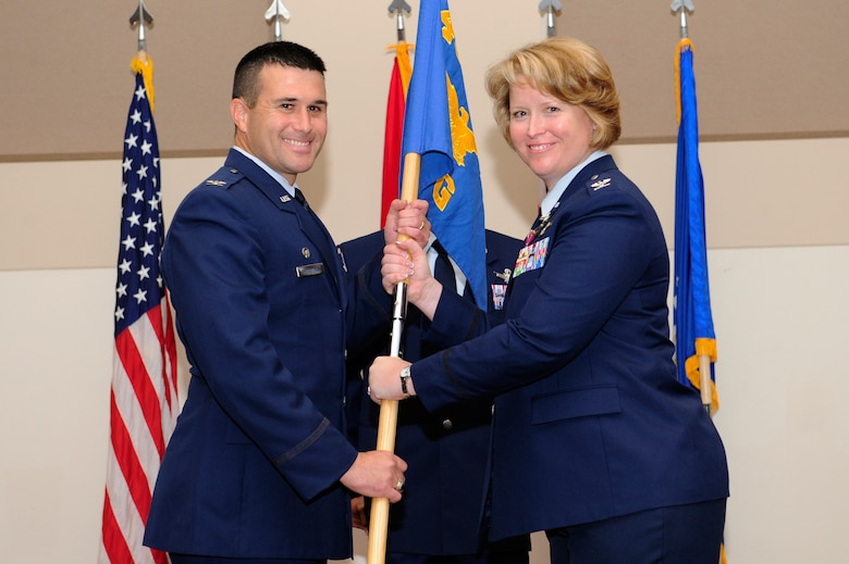 Col. DeAnna Burt, right, relinquishes command of the 460th Operations Group to Col. John Wagner, 460th Space Wing commander, during the 460th OG change of command ceremony Aug. 12, 2014, at the Leadership Development Center on Buckley Air Force Base, Colo. The event signaled Col. Michael Jackson, 460th OG commander, assuming command from Burt, who served as commander of the 460th OG for two years. (U.S. Air Force photo by Airman 1st Class Samantha Saulsbury/Released)