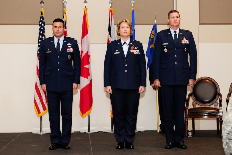 From left, Col. John Wagner, 460th Space Wing commander, Col. Michael Jackson, 460th Operations Group commander and Col. DeAnna Burt, outgoing 460th OG commander, stand at attention during the 460th OG change of command ceremony Aug. 12, 2014, at the Leadership Development Center on Buckley Air Force Base, Colo. Jackson assumed command from Burt, who served as commander of the 460th OG for two years. (U.S. Air Force photo by Airman 1st Class Samantha Saulsbury/Released)