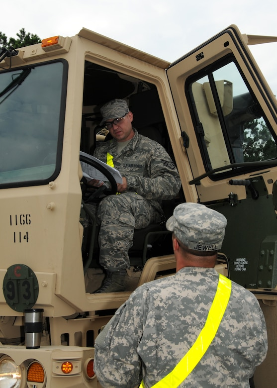 Army Sgt. Jewell oversees Air Force Staff Sgt. Brian Silva performing morning maintenance checks on a light/medium tactical vehicle (LMTV) prior to driving on Aug. 6 here.  Staff Sgt. Silva was the only member from the 267th Combat Communications Squadron to attend the first course taught by the 1166th Transportation Company on the maintenance and operation of the LMTVs.  (U.S. Air National Guard photo by Tech. Sgt. Lindsey Sarah Watson-Kirwin /Released)