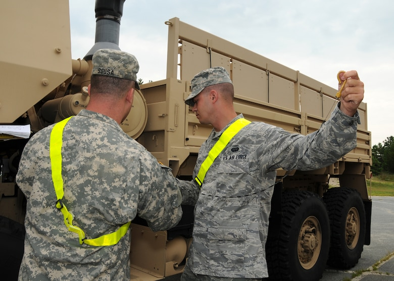 Air Force Staff Sgt. Brian Silva, 267th Combat Communications Squadron, and Army Sgt. Sousa, 1166th Transportation Company, perform maintenance checks on a light/medium tactical vehicle prior to their driving training on Aug. 6 here.  (U.S. Air National Guard photo by Tech. Sgt. Lindsey Sarah Watson-Kirwin /Released)
