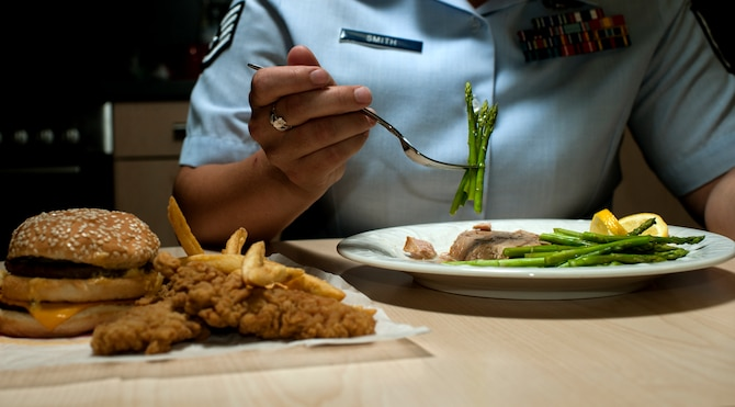 U.S. Air Force Staff Sgt. India Smith, 372nd Training Squadron Detachment 17 NCO in charge of knowledge operations from Ottawa, Kan., eats asparagus and fish during lunch Aug. 11, 2014, at Spangdahlem Air Base, Germany. Smith balances healthy eating is a tool to accomplish her goal of scoring in the excellent category for her physical fitness test. (U.S. Air Force photo by Senior Airman Rusty Frank/Released)