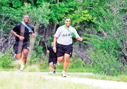 Capt. Jabari Jackson, left, and 1st Sgt. Patrick Lockett, commander and senior noncommissioned officer with Troop B, 5th Sqdn., 4th Cav. Regt., navigate the hill run portion of the squadron's St. Marcouf PT event July 17 at Fort Riley.