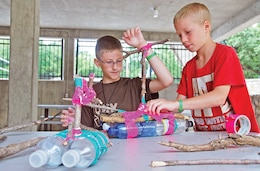 From left, Randal Smith, 11, and Ridley Swadeo, 10, construct a boat out of bottles, twigs and duct tape during Camp Corral at the Rock Springs 4-H, Junction City. The weeklong camp is geared specifically for military children.