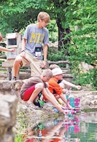Counselors help campers launch homemade boats during Camp Corral at the Rock Springs 4-H, Junction City. The weeklong camp, geared specifically for military children, featured activities such as crafts, archery, horseback riding and more.