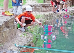 Chase Ream, 10, launches a homemade boat during Camp Corral at the Rock Springs 4-H in Junction City.
