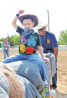 Garrison Commander Col. Andrew Cole, right, rocks Steven Dyson, 6, left, on a hand-powered mechanical bull during the Special Needs Rodeo July 19 at the Geary County 4-H Fairgrounds.