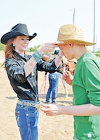 Samuel Lafleur, 20, right, has his cowboy hat adjusted by a rodeo queen candidate during the Special Needs Rodeo July 19 at the Geary County 4-H Fairgrounds.