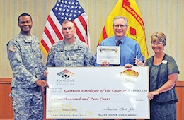 The garrison command team awards Matthew Allain, electronic technician, DPTMS, second from right, with a $1,000 check after being named Employee of the Quarter during an Installation Awards Ceremony July 17 at Riley's Conference Center.