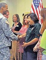 Marti Oliveras, administrative support assistant, Fort Riley Education Services, right, receives a certificate of appreciation for her contributions to the education services team from Garrison Commander Col. Andrew Cole, left, during an Installation Awards Ceremony July 17 at Riley's Conference Center.