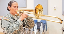 "Spc. Amanda DiClerico, 1st Inf. Div. Band, plays her tenor trombone July 10 in the band's headquarters building. DiClerico has only been with the band for a few weeks, but she has been playing the instrument since she was 11. ""I come from a very military-oriented town,"" said the Virginia Beach, Va., native. ""The Army, the Marines and the Navy have their school of music there, so I've studied with various military musicians throughout my life. I knew coming out of college that was something I'd like to do as well."""