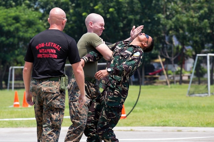 MARINE BARRACKS RUDIARDO BROWN, Philippines – Cpl. Christopher Schumacher, a fiscal budget technician with U.S. Marine Corps Forces, Pacific performs a Mechanical Advantage Control Hold after being sprayed with Oleoresin Capsicum, during a demonstration of Non-lethal Weapons techniques, August 14. NOLES is an annual field-training exercise and leadership seminar sponsored by U.S. Marine Corps Forces, Pacific, and hosted by various nations throughout the Asia-Pacific. This is the 13th iteration of NOLES with members from the AFP, and Philippine National Police participating.