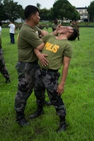 FORT BONIFACIO, Philippines – Police Officer Rafael B. Muchuelas, a lead instructor with the Philippine National Police (PNP), performs a Mechanical Advantage Control Hold (MACH) on Jonathan Catig, a police inspector with the PNP, Aug. 4, during Non-Lethal Weapons Executive Seminar 2014. NOLES is an annual field-training exercise and leadership seminar sponsored by U.S. Marine Corps Forces, Pacific, and hosted by various nations throughout the Asia-Pacific.  This is the 13th iteration of NOLES with members from the AFP, and Philippine National Police participating.