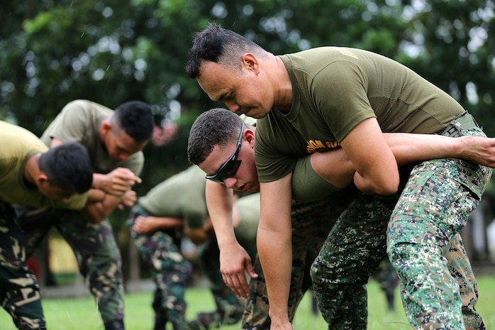 Philippine Marine Corps Staff Sgt. Eric Castino performs mechanical advantage control holds on U.S. Marine Corps Lance Cpl. Joshua Rodriguez, with 3rd Law Enforcement Battalion, III Marine Headquarters Group, at Fort Bonifacio, Philippines Aug. 04, 2014 during the Non-Lethal Weapons Executive Seminar field training exercise. The effective use of non-lethal weapons can be extremely valuable during rescue missions, for force protection in civil disturbances, while controlling rioting and prisoners of war, for checkpoint or convoy operations, HA/DR operations, or in situations in which civilians are used to mask a military attack.