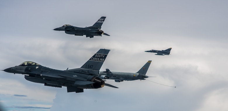 Two South Carolina Air National Guard F-16s fly alongside a Colombian air force Kfir and KC-767 tanker aircraft during a training flight Aug. 12 over Colombia. Nearly 100 Airmen and six F-16s from the 169th Fighter Wing at McEntire Air National Guard Base are participating in the combined air operation engagement, which is the first major joint-air engagement opportunity under the auspices of the South Carolina's State Partnership Program with Colombia. The exercise allows the U.S. and Colombian airmen to share tactics, techniques, and procedures on many subjects including defensive air operations, operations coordination and scheduling, and best maintenance practices; all of which can be applied to maritime, littoral waters, over-land areas of operations, and defense of national territory. (U.S. Air Force photo by Maj. Matt Booth/Released)