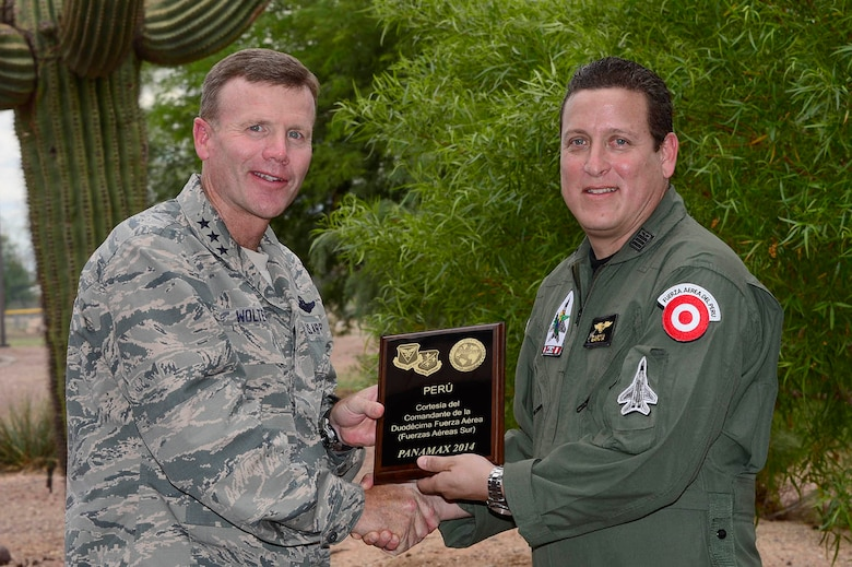 Lt. Gen. Tod Wolters, 12th Air Force (Air Forces Southern) commander, presents a PANAMAX 2014 participation plaque to Lt. Col. Antonio Garcia, Peru's senior officer participating in the exercise, during a recognition ceremony at Davis-Monthan AFB, Ariz., Aug. 14, 2014. Twenty-eight service members from six partner nations worked alongside their 12th AF (AFSOUTH) counterparts at Davis-Monthan during PANAMAX 2014. (U.S. Air Force photo by Tech. Sgt. Heather R. Redman/Released)