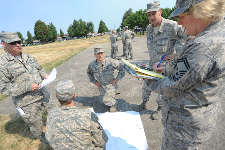 Senior Master Sgt. Linda Baugher, far right, a Wing Inspection Team member takes notes after receiving feedback from the 142nd Fighter Wing Civil Engineer Squadron has evacuated a building during an exercise conducted by the Wing Inspection Team, Aug. 2, 2014, Portland Air National Guard Base, Ore. (U.S. Air National Guard photo by Tech. Sgt. John Hughel, 142nd Fighter Wing Public Affairs/Released)