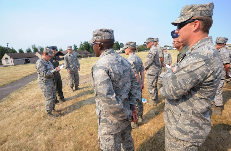 Chief Master Sgt. Michele Marshall, far left, goes through a roll call of Medical Group staff members after a build evacuation drill as part of the exercise conducted by the Wing Inspection Team, Aug. 2, 2014, Portland Air National Guard Base, Ore. (U.S. Air National Guard photo by Tech. Sgt. John Hughel, 142nd Fighter Wing Public Affairs/Released)