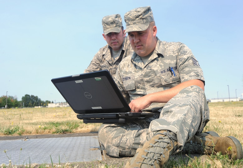 Oregon Air National Guardsmen Tech. Sgt. Matthew Shifflette, left, and Tech. Sgt. Mark (Gus) Johnson, right, use a laptop computer to continue their work after a building evacuation drill during an exercise conducted by the Wing Inspection Team, Aug. 2, 2014. Both Shifflette and Johnson are maintenance specialist assigned to the 142nd Fighter Wing Commutations Flight. (U.S. Air National Guard photo by Tech. Sgt. John Hughel, 142nd Fighter Wing Public Affairs/Released)