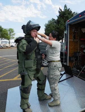Explosive Ordinance Disposal Specialist Tech. Sgt. Jason Ganner, left, has help with his EOD 9 suit from Staff Sgt. Rachel Fleming, right, during a Wing Inspection Team exercise, Aug. 1, 2014 at the Portland Air National Guard Base, Ore. Both members are assigned to the 142nd Fighter Wing Civil Engineer Squadron. (U.S. Air National Guard photo by Lt. Col. Frank Page, courtesy 142nd Fighter Wing Inspection Team/Released)