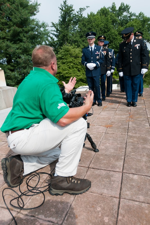 A CBS Sports videographer shoots footage of a joint-service Color Guard Team comprised of Kentucky Air and Army National Guard members at Frankfort Cemetery in Frankfort, Ky., on Aug. 5, 2014. The television spot was broadcast during the network's national coverage of the Professional Golfers' Association of America Championship at Valhalla Golf Club in Louisville, Ky., Aug. 4-10. (U.S. Air National Guard photo by Master Sgt. Phil Speck)