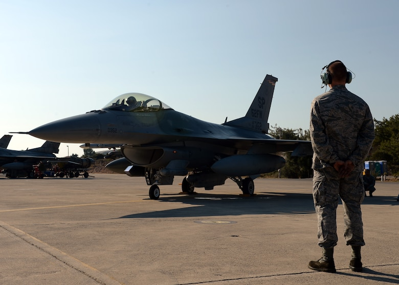 U.S. Air Force Senior Airman Alan Nelson, 52nd Aircraft Maintenance Squadron's 480th Aircraft Maintenance Unit  and native of Pensacola, Fla., watches the F-16 Fighting Falcon fighter aircraft of U.S. Air Force Col. Pete Bilodeau, 52nd Fighter Wing commander, during a bilateral training event in Souda Bay, Greece, Aug. 12, 2014. Bilodeau flew out to Souda Bay from Spangdahlem Air Base, Germany, to meet with the Hellenic air force's 115th Combat Wing commander and participate in one of the initial days of the training. (U.S. Air Force photo by Staff Sgt. Daryl Knee/Released)