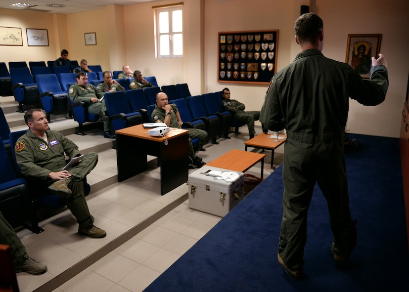 A pilot from the 480th Fighter Squadron from Spangdahlem Air Base, Germany, briefs a group of U.S. and Greek pilots Aug. 12, 2014, before a flying mission at the bilateral training event in Souda Bay, Greece. The pilots attend the mass briefing to clarify the objectives of the day's training and to receive the latest information on the weather and threat intelligence. (U.S. Air Force photo by Staff Sgt. Daryl Knee/Released)
