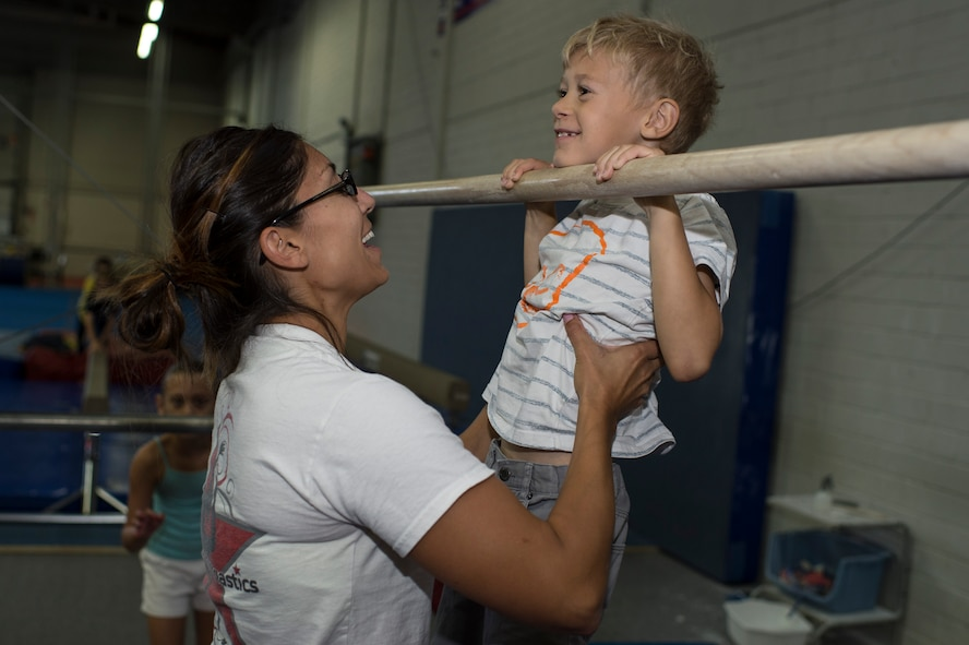 Cat Schnoes, gymnastics coach, wife of Tech. Sgt. Karl Schnoes, 52nd Civil Engineer Squadron firefighter, assists Logan Black, son of Jessica Black, to perform a pull-up during the Exceptional Family Member Program camp at Bitburg Annex, Germany, Aug. 12, 2014. The EFMP family support coordinator helps families identify and access programs and services for their child's need. (U.S. Air Force photo by Staff Sgt. Christopher Ruano/Released)
