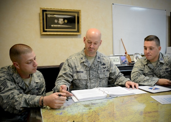 Col. Mark Anarumo, 39th Air Base Wing vice commander, discusses daily operations with Staff Sgt. Robert Wayland, 39th ABW command chief executive assistant (left),  and Capt. Thomas Uhl (right), 39th ABW executive officer, Aug. 12, 2014, Incirlik Air Base, Turkey. As vice commander, he is responsible for approximately 5,000 U.S. military, civilian and contractor personnel and the combat readiness of U.S. Air Force units at Incirlik and two geographically-separated units in Turkey. (U.S. Air Force photo by Staff Sgt. Veronica Pierce)