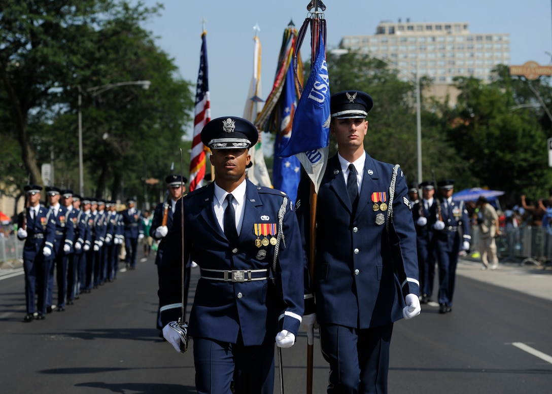 Maj. Scott Belton, left, and Senior Airman Nicholas Priest lead the U.S. Air Force Color Team and ceremonial guardsmen August 9, 2014, during the Bud Billiken Parade in Chicago. Belton is the assistant director of operations and Priest is a member of the Color Flight Team within the U.S. Air Force Honor Guard. (U.S. Air Force photo/Senior Airman Nesha Humes)