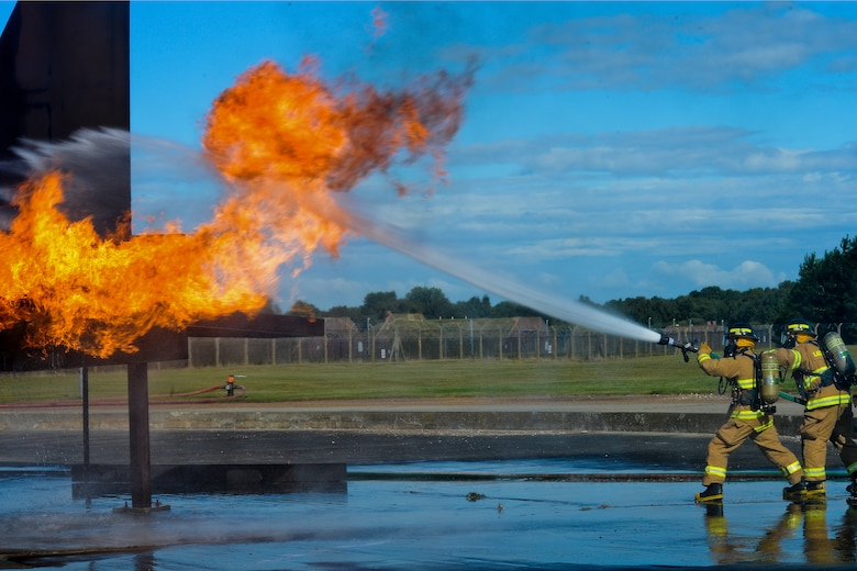 Firefighters of the 48th Civil Engineer Squadron Fire Department spray a mock F-15 Eagle engine with water during live-fire training Aug. 13, 2014, at the burn pit on Royal Air Force Lakenheath, England. All firefighters are required to conduct live-fire training twice a year to avoid skill fade and keep their qualifications current. (U.S. Air Force photo/Airman 1st Class Trevor T. McBride)