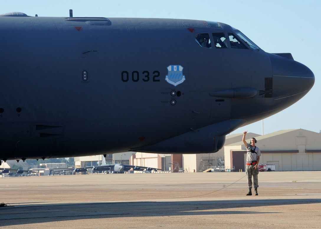 Senior Airman Mitchell Dexter, 2nd Aircraft Maintenance Squadron crew chief, communicates with aircrew in the cockpit of a B-52H Stratofortress during a Minimum Interval Takeoff on Barksdale Air Force Base, La., Aug. 14, 2014. A MITO is executed to allow the B-52 to quickly respond and deliver precision munitions at a momentÕs notice. Starter cartridges, filled with gun powder, are used during this takeoff instead of the standard, compressed-air takeoff.  (U.S. Air Force photo/Staff Sgt. Sean Martin)
