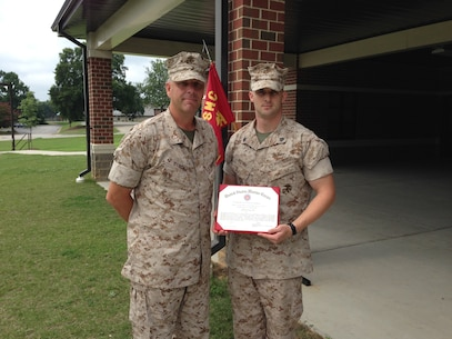 CWO4 Matthew Studer, Executive Officer of Alpha Company, Marine Corps Detachment Fort Lee, and Sgt Justin Brown, Aerial Delivery Instructor, with Sgt Brown's Certificate of Commendation for being selected as the Instructor of the Quarter for Alpha Company.  (Photo provided by CWO4 Allen Ostermann, Marine Corps Detachment Public Affairs Officer/Released)