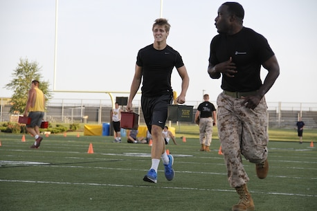 Beau A. Bequeaith, a senior Blue Valley High School Tigers tight end, grimaces as he sprints with two 30-pound ammunition cans as part of the Marine Corps Combat Fitness Test as Sgt. Laronald McKinney, a Marine Corps Recruiting Station Kansas City, Recruiting Sub-Station Olathe recruiter, sprints ahead to motivate Bequeaith to the end. The CFT is substantially different from a normal regiment of football and was seen as a way to shake up the usual routine pf practice before the season starts.