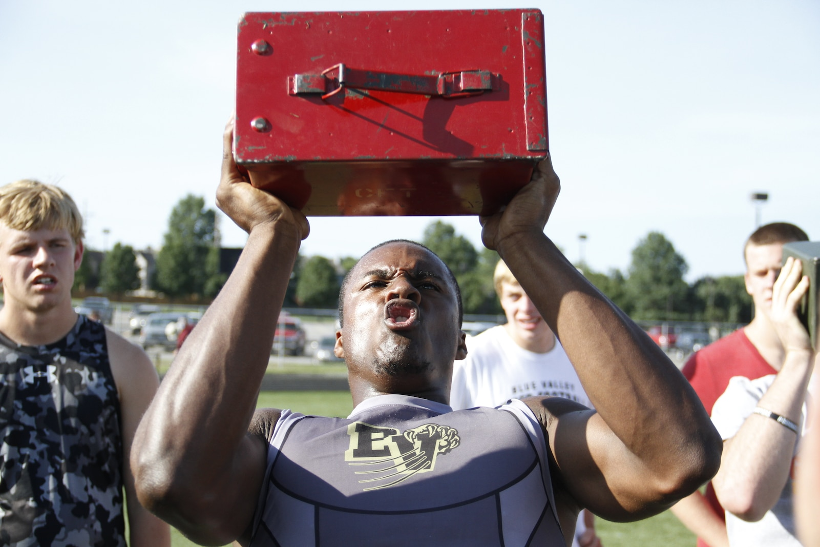 Gannon C. Cornley, a senior Blue Valley High School Tigers cornerback, running back, and wide receiver, exhales sharply as he presses a 30-pound ammunition can over his head during the Marine Corps' Combat Fitness Test as part of the Tigers offseason training at the Lamar District Athletic Complex Aug. 14, 2014. Marines from Marine Corps Recruiting Sub-Station Olathe were on hand to administer and supervise the CFT. Cornley performed more than 140 ammo-can lifts in the alloted two minutes.