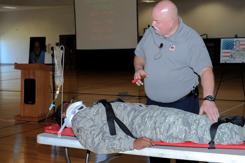 Airman 1st Class Nicholas Thomas, 2nd Space Warning Squadron, assists Greg McCarty, Tampa Fire Rescue paramedic, with the Street Smart presentation during the Team Buckley Safety Day Aug. 12, 2014, at the base fitness center on Buckley Air Force Base, Colo. Street Smart showcased the events that transpire after making a bad decision and getting behind the wheel of a car. (U.S. Air Force photo by Airman 1st Class Samantha Saulsbury/Released)