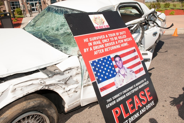 A crushed car and a stark reminder of the dangers of drinking and driving were placed outside the base fitness center during the Team Buckley Safety Day Aug. 12, 2014, on Buckley Air Force Base, Colo. Safety day consisted of presentations and stories designed to raise awareness of the dangers of making poor decisions on the road. (U.S. Air Force photo by Airman 1st Class Samantha Saulsbury/Released)