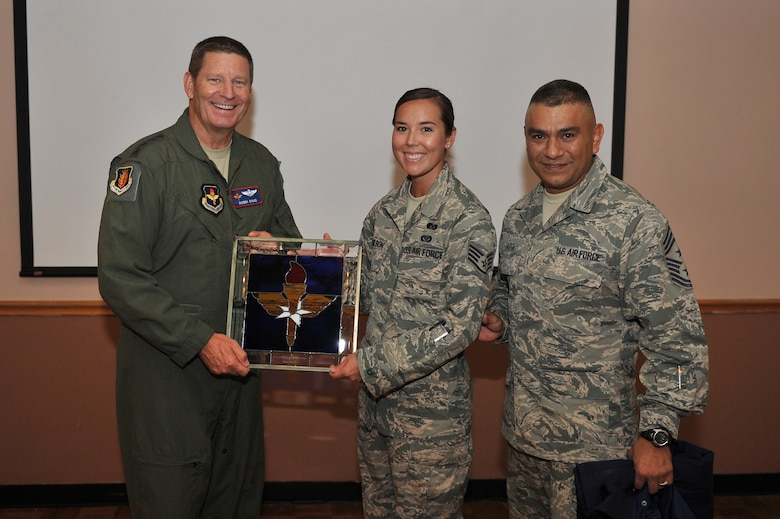 ALTUS AIR FORCE BASE, Okla. – U.S. Air Force Gen. Robin Rand, commander of Air Education and Training Command, and U.S. Air Force Chief Master Sgt. Gerardo Tapia, Air Education and Training Command command chief, present a gift to the 2014 AETC Outstanding Airman of the Year, Staff Sgt. Jessica Paulson, 97th Civil Engineering Squadron. Paulson was deployed as a Senior Airman when she earned the award.  (U.S. Air Force photo by Senior Airman Dillon Davis/Released)