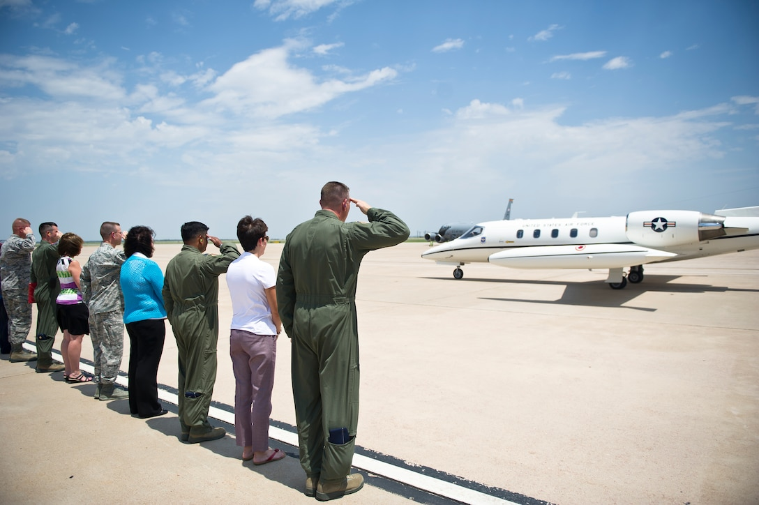 ALTUS AIR FORCE BASE, Okla. – Leaders of the 97th Air Mobility Wing salute the aircraft transporting U.S. Air Force Gen. Robin Rand, commander of Air Education and Training Command, as he arrives on the flightline Aug. 6, 2014. During the visit, Rand, Mrs. Rand and U.S. Air Force Chief Master Sgt. Gerardo Tapia, AETC command chief, were able to see Altus AFB and meet some of the top performing Airmen. (U.S. Air Force photo by Senior Airman Dillon Davis/Released)