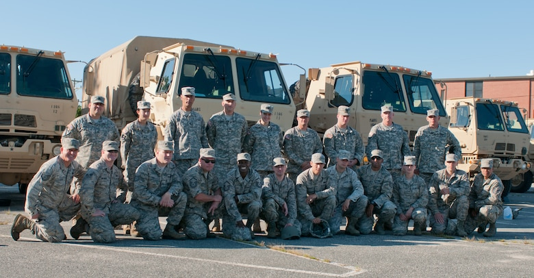 Airmen from the 102nd Intelligence Wing pose with members of the 1166th Transportation Company in front of light/medium tactical vehicles (LMTV) on Aug. 12, 2014 at Joint Base Cape Cod. The Mass. Air Guard airmen were receiving training from the Mass. Army Guard soldiers on the maintenance and operation of the LMTVs. (U.S. Air National Guard photo by Master. Sgt. Aaron Smith /Released)