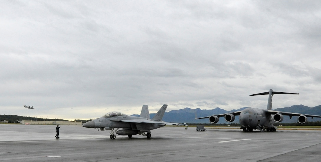 An F-18 Hornet returns from a mission, an F-22 Raptor takes to the skies, and a C-17 Globemaster prepares for a mission during Red Flag-Alaska 14-3 Aug. 8. Red Flag-