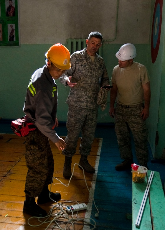 Mongolian armed forces Sgt. Erdentsgot Batchulcuun, a MAF electrician (left), reviews equipment as Senior Master Sgt. Sandy Miller (center) and  Tech. Sgt. Brede Grorud discuss the electrical system in a elementary school Aug. 15, 2014, in Bulgan, Mongolia. Operation PACANGEL helps cultivate common bonds and foster goodwill between the U.S., Mongolia and regional nations by conducting multilateral humanitarian assistance and civil military operations.  Miller and Grorud are civil engineers assigned to the 354th Civil Engineer Squadron, Eielson Air Force Base, Alaska. (Air Force photo/Staff Sgt. William Banton)