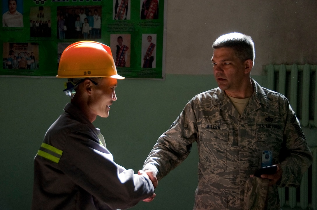Mongolian armed forces Sgt. Erdentsgot Batchulcuun, a mongolian electrician (left), greets Senior Master Sgt. Sandy Miller in an elementary school Aug. 13, 2014, during Operation Pacific Angel 14-4 in Bulgan, Mongolia. Operation PACANGEL helps cultivate common bonds and foster goodwill between the U.S., Mongolia and regional nations by conducting multilateral humanitarian assistance and civil military operations. Miller is a senior engineering lead assigned to 354th Civil Engineer Squadron, Eielson Air Force Base, Alaska. (Air Force photo/Staff Sgt. William Banton)