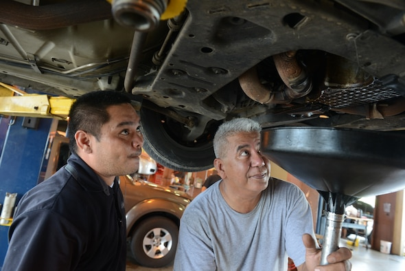 Jason Mesa (left) Andersen auto skills center mechanic, assists a member of Team Andersen to change his oil Aug. 15, 2014, on Andersen Air Force Base, Guam. The shop gives people a place to work on their vehicles with assistance from trained automotive mechanics. (U.S. Air Force photo by Airman First Class Adarius Petty/Released)