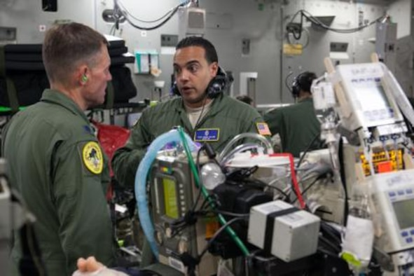 Lt. Col. Patrick Johannes, left, and Tech. Sgt. Eddie Colon, both assigned to the 10th Expeditionary Aeromedical Evacuation Flight, discuss a patient's care during a flight from Ramstein Air Base, Germany, July 4, 2014. Johaness and Colon are members of a Critical Care Air Transport Team. (U.S. Air National Guard photo by Staff Sgt. Allan Eason/Released)