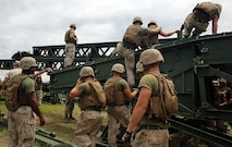 Marines with 8th Engineer Support Battalion, 2nd Marine Logistics Group work with personnel from 9th Engineer Support Battalion, 3rd Marine Logistics Group to climb onto the medium girder bridge to remove panels and pull the bridge into place during bridge assembly training at Camp Lejeune, N.C. Aug. 5, 2014. Marines with 9th ESB cross-trained with 8th ESB to develop their proficiency in bridging. (U.S. Marine Corps photo by Lance Cpl. Kaitlyn Klein/released)