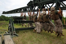 Marines with 8th Engineer Support Battalion, 2nd Marine Logistics Group work with personnel from 9th Engineer Support Battalion, 3rd Marine Logistics Group to pull down on the nose of the medium girder bridge as they lock everything in place during bridge assembly training at Camp Lejeune, N.C. Aug. 5, 2014. This training maintained gap-crossing capabilities and developed proficiency in bridging. (U.S. Marine Corps photo by Lance Cpl. Kaitlyn Klein/released)