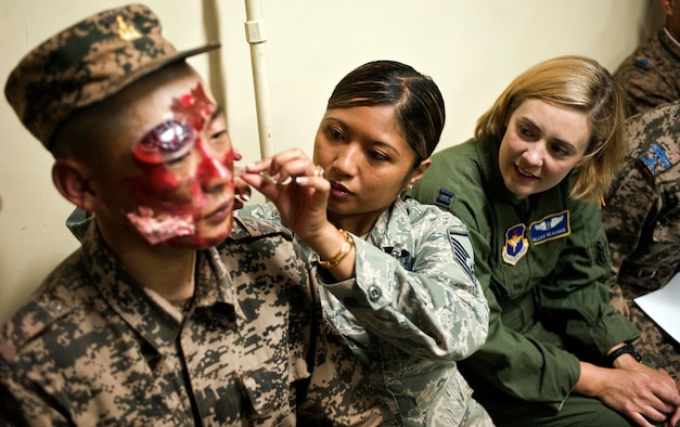 U.S. Air Force Master Sgt. Victoria Grey, middle, and Capt. Alexis Beauvais moulage a member of the Mongolian armed forces as part of mass casualty response training during Operation Pacific Angel 14-4 Mongolia, Aug. 8 2014, in Ulaanbaatar, Mongolia. Operation PACANGEL helps cultivate common bonds and fosters goodwill between the U.S., Mongolia and regional nations by conducting multilateral humanitarian assistance and civil military operations. Grey and Beauvais are medical subject matter expert instructors. (U.S. Air Force photo/Staff Sgt. William Banton)